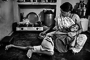 Suraj Pratap Singh, 18, a boy affected by severe cerebral palsy, is being fed by his mother, Kaser Bai, 40, a '1984 Gas Survivor', while inside their home in Chola, one of the water-affected colonies in Bhopal, Madhya Pradesh, central India, near the abandoned Union Carbide (now DOW Chemical) industrial complex.