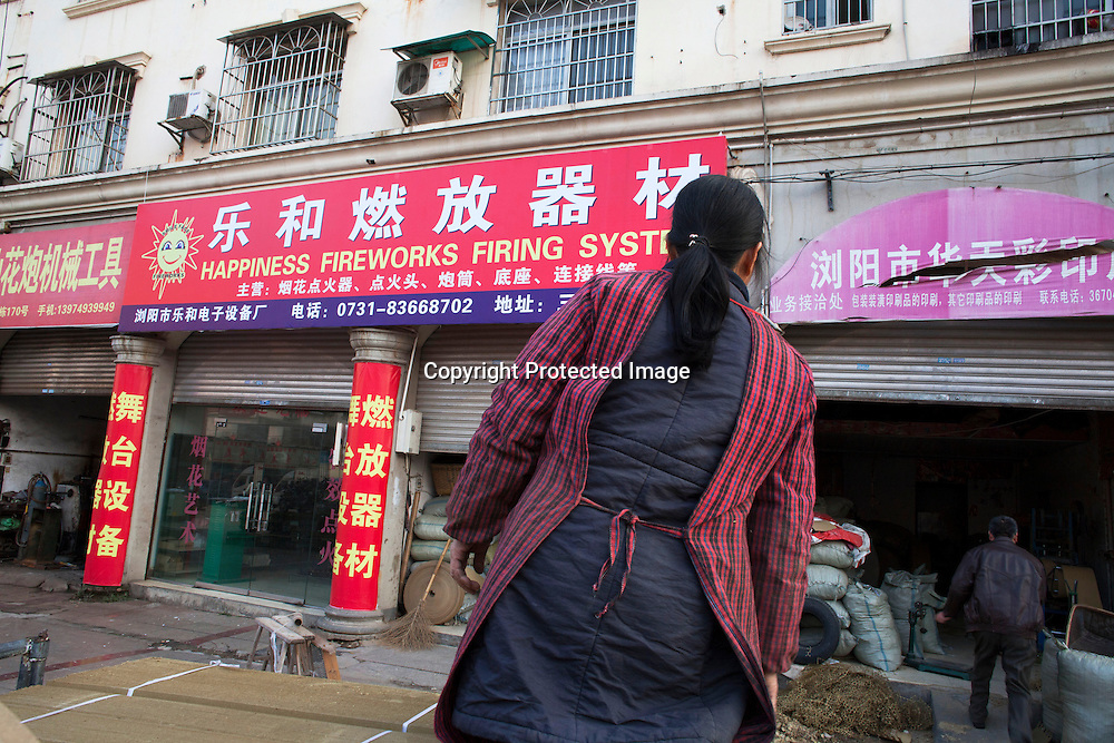 "Hunan, Liuyang, Dec. 19, 2013 : Mrs. Zhu. an employee that produces  firecracker lits ,unloads cardboxes at the ""Liuyang  interational firecrackers exhibition and trade city "" which is    a local wholesale market for the firecracker industry."