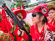 19 MAY 2013 - BANGKOK, THAILAND:  A Thai Red Shirt with a toy gun to protest Thai Army violence against the Red Shirts during a Red Shirt rally in Ratchaprasong Intersection honoring Red Shirts killed by the Thai army in 2010. More than 85 people, most of them civilians, were killed during the Thai army crackdown against the Red Shirt protesters in April and May 2010. The Red Shirts were protesting against the government of Abhisit Vejjajiva, a member of the opposition who became Prime Minister after Thai courts ruled the Red Shirt supported government was unconstitutional. The protests rocked Bangkok from March 2010 until May 19, 2010 when Thai troops swept through the protest areas arresting hundreds.     PHOTO BY JACK KURTZ