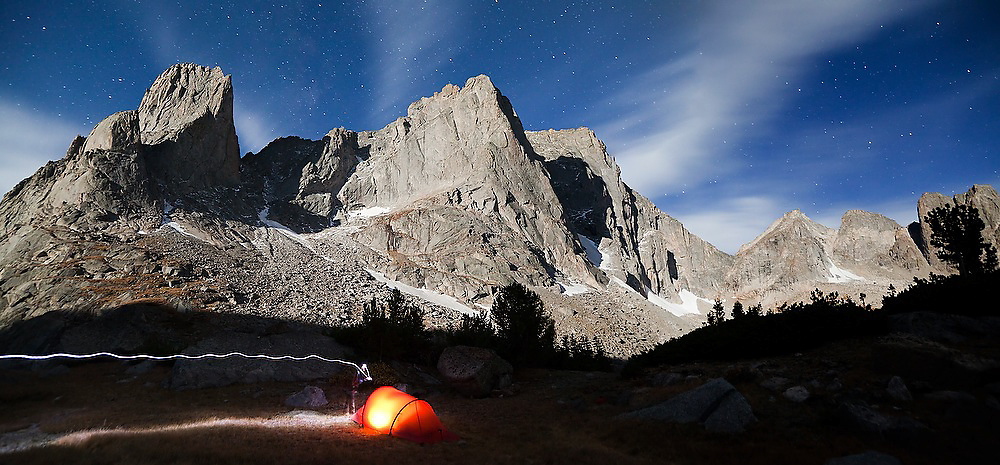Moonlight illuminates Warrior and War Bonnet Peaks above a glowing tent in in the Cirque of the Towers, Popo Agie Wilderness, Wind River Range, Wyoming.