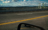 Tacoma Narrows Bridges viewed from and eclipsed by a highway overpass of Jackson Avenue in Tacoma Washington, USA