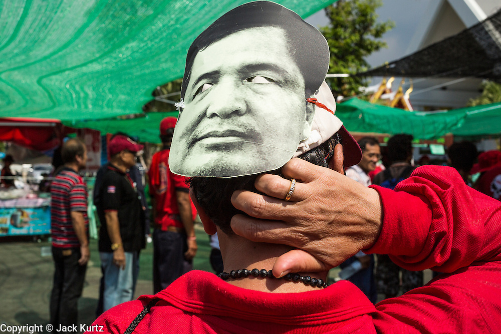 01 MAY 2013 - BANGKOK, THAILAND:   A Thai Red Shirt scratches his neck while he wears a mask of former Prime Minister Yingluck Shinawatra during rally and protest at the Constitutional Court in Bangkok. Several hundred Thai Red Shirts, members of the United Front for Democracy against Dictatorship (UDD), have been camped out at Thailand's Constitutional Court, which oversees matters related to the Thai constitution and constitutional amendment. The Red Shirts are protesting the court's decision to consider a petition regarding the constitutionality of the constitutional amendments that have been proposed by the government. The group is arguing that by considering the petition, the Court is impeding the powers of the legislative branch. PHOTO BY JACK KURTZ
