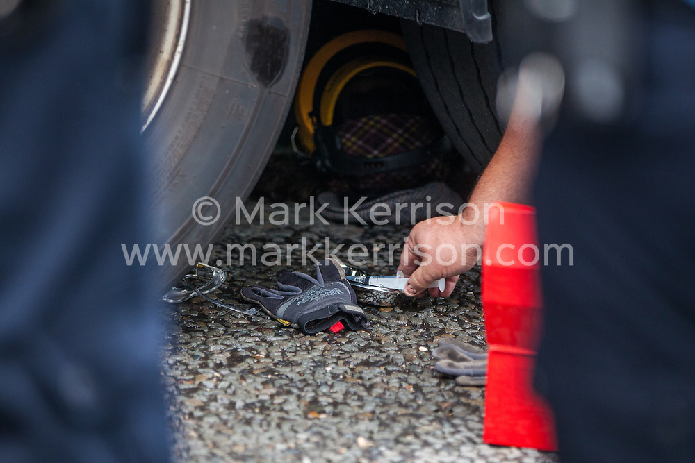 London, UK. 6 September, 2019. Metropolitan Police officers work to remove an activist locked beneath a truck making a delivery to ExCel London for DSEI, the world's largest arms fair. The road remained blocked for several hours. The fifth day of protests against the arms fair was themed as Stop The Arms Fair: Stop Climate Change in order to highlight links between the fossil fuel and arms industries.
