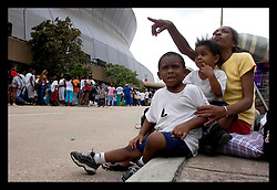 28th August, 2005. Hurricane Katrina, New Orleans, Louisiana. Gwendolyn Maguire with her children Ronjae, 2yrs and Ron, 3yrs wait with all their belongings outside the Superdome.