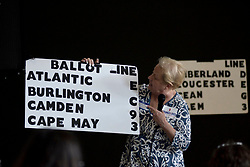 Campaign volunteer Helen Duda holds a board  indicating the candidate's position on the eight different ballots for the upcoming Primaries. (Bastiaan Slabbers/ for WHYY)