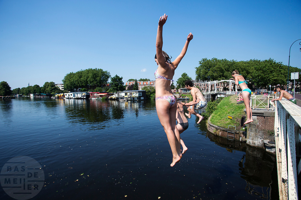 Jongeren springen vanaf de Muntbrug in Utrecht het verkoelende water van het Merwedekanaal in. Op waarschijnlijk de laatste mooie zomerse dag genieten mensen nog volop van de zon.<br /> <br /> Young people are jumping of a bridge in Utrecht into the cool water of the Merwedekanaal.