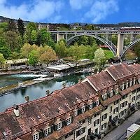 Scenic Western View of Bern, Switzerland <br /> This scenic, western view of Bern from the platform of the Cathedral of St. Vincent gives you a glorious look at the row houses along Aarstrasse, the Aare River and a tram crossing the Kirchenfeldbrücke. The bridge was built in 1883. On the left are the spires of the Bernisches Historisches Museum.