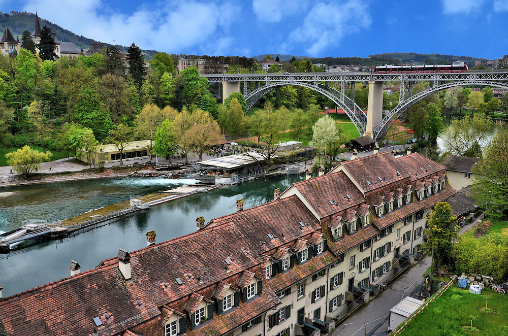 Elevated, Scenic, Western View of Bern, Switzerland <br /> This scenic, western view of Bern from the platform of the Cathedral of St. Vincent gives you a glorious look at the row houses along Aarstrasse, the Aare River and a tram crossing the Kirchenfeldbr&uuml;ck bridge which was built in 1883.  On the left are the spires of the Bernisches Historisches Museum.