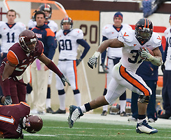 Virginia running back Cedric Peerman (37) rushes for extra yardage after breaking a tackle from Virginia Tech cornerback Victor Harris (1).  The Virginia Tech Hokies defeated the Virginia Cavaliers 17-14 in NCAA football at Lane Stadium on the campus of Virginia Tech in Blacksburg, VA on November 29, 2008.