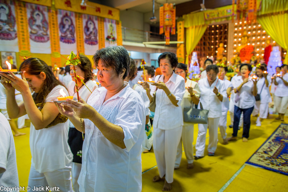 23 OCTOBER 2012 - HAT YAI, SONGKHLA, THAILAND: People process through the temple during a service on the last day of the Vegetarian Festival at Wat Ta Won Vararum, a Chinese Buddhist temple in Hat Yai. The Vegetarian Festival is celebrated in Thai-Chinese communities throughout Thailand. It is the Thai Buddhist version of the The Nine Emperor Gods Festival, a nine-day Taoist celebration celebrated in the 9th lunar month of the Chinese calendar. For nine days, those who are participating in the festival dress all in white and abstain from eating meat, poultry, seafood, and dairy products. Vendors and proprietors of restaurants indicate that vegetarian food is for sale at their establishments by putting a yellow flag out with Thai characters for meatless written on it in red.  PHOTO BY JACK KURTZ