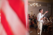 14 SEPTEMBER 2011 - SUN LAKES, AZ: An American flag frames Mitt Romney (CQ) while he speaks at the Oakwood Clubhouse at Sun Lakes Wednesday. Romney was one of the first of the 2012 Republicans running for the GOP Presidential nomination to come to Arizona. He campaigned Wednesday in Tucson and Sun Lakes and attended a private event in Tempe.     PHOTO BY JACK KURTZ
