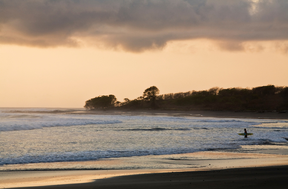A lone surfer walks into the water for a sunset surf session in Marbella Costa Rica.