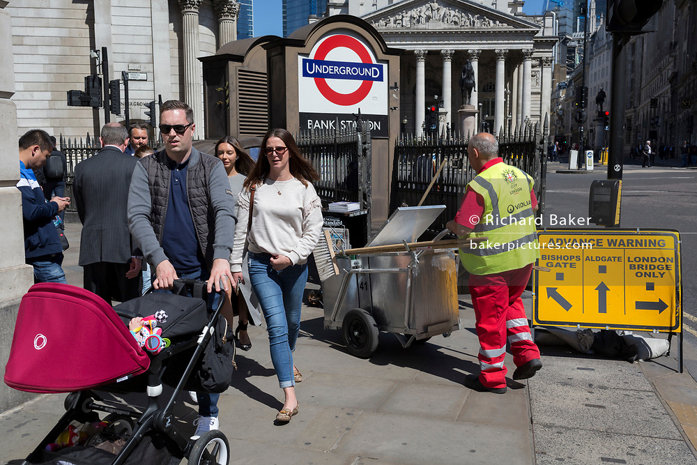 A street cleaning contractor and parents push their respective cart and pushchair outside one entrance of Bank Underground Station in the City of London, the capital's ancient, financial district, on 14th May, in London, England.
