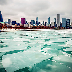 Chicago winter skyline picture with frozen ice on Lake Michigan and snow on the lakefront.