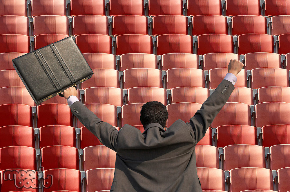 Back view of victorious businessman with briefcase facing rows of red seats at stadium