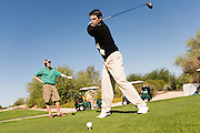 Golfer Teeing Off While Friend Watches