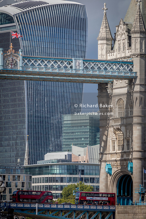 As London buses cross the Thames river, the British Union Jack flag flies from the upper gantry of Victorian-era Tower Bridge, near the modern Walkie Talkie building (aka 20 Fenchurch Street), on 14th September 2017, in London, England.