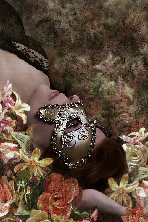 femaly lying back in a bed of flowers, wearing a mask