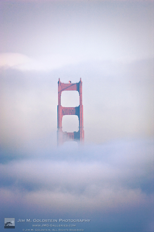 The south tower of the Golden Gate Bridge rises out of the fog on an early winter morning.