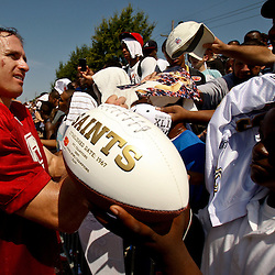 July 31, 2010; Metairie, LA, USA; New Orleans Saints quarterback Drew Brees (9) signs autographs for fans following a training camp practice at the New Orleans Saints practice facility. Mandatory Credit: Derick E. Hingle