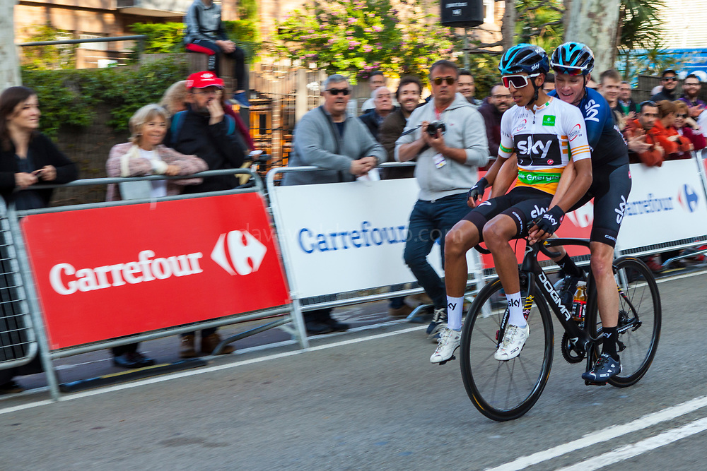 Egan Bernal hitching a handlebar ride from Chis Froome following Stage 5 of 2019 Volta Catalunya.<br /> <br /> Bicycle made for two: Chris Froome gives a ride to Egan Bernal after the latter had a mechanical fault int he final kilometre of Stage 5 of the Volta Catalunya 2019, into Sant Cugat del Valles