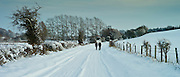 Walkers in snow-covered  lane in the Windrush valley, Swinbrook, The Cotswolds
