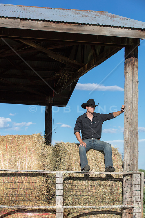 All American cowboy sitting on a hay bale in a barn at sunset