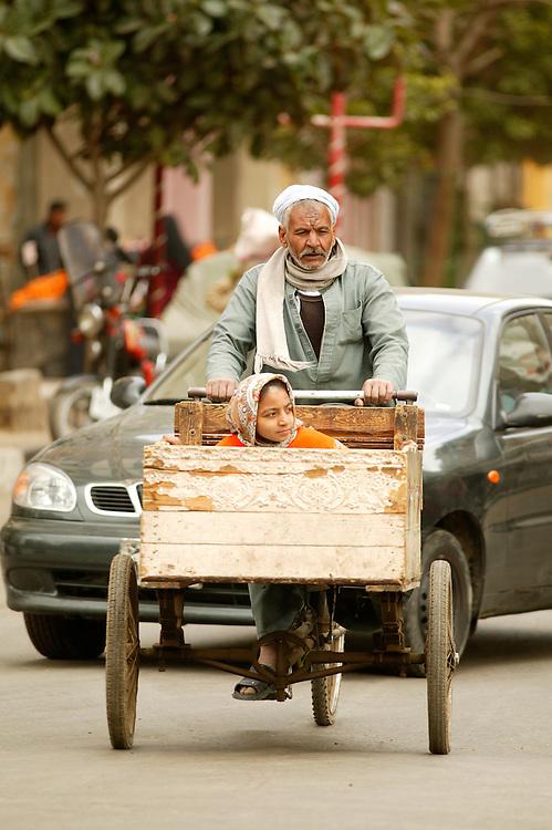 En eldre mann psykkel med barnebarnet i en kasse foran.