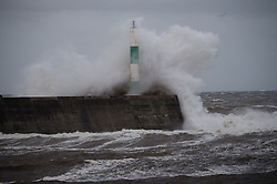 """© Licensed to London News Pictures. 21/10/2014. Aberystwyth Wales. At daybreak on Tuesday 21 October 2014, gale force winds and a high tide combine to bring waves crashing into the harbour walls at Aberystwyth, Ceredigion west Wales UK. <br /> The tail-end of Hurricane Gonzalo produced heavy overnight rain with winds on the coast gusting up to 70mph in the early morning. A yellow 'be aware' warning has been issued by the Met Office for the whole of Wales, warning of """"potential disruption to travel and damage to trees"""" photo © keith morris / LNP"""