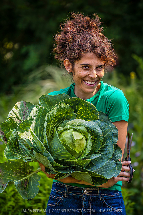 A healthy young woman gardener with curly reddish hair, holds a large, freshly harvested cabbage and grins at the camera.
