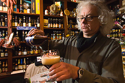 Dirk Van Dyck, proprietor of the Kulminator Bar, in Antwerp, Belgium, pours a glass of Chimay Blue, one of Belgium's most popular Trappist beers. The Kulminator has a reputation as being one of the best beer bars in the world. (Photo © Jock Fistick)