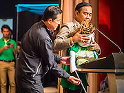 10 JANUARY 2015 - BANGKOK, THAILAND: A member of his staff (back to camera) helps General PRAYUTH CHAN-OCHA, the Prime Minister of Thailand, with a puppet while the Prime Minister talks to children about being good citizens during National Children's Day celebrations at Government House in Bangkok. National Children's Day falls on the second Saturday of the year. Thai government agencies sponsor child friendly events and the military usually opens army bases to children, who come to play on tanks and artillery pieces. This year Thai Prime Minister General Prayuth Chan-ocha, hosted several events at Government House, the Prime Minister's office.    PHOTO BY JACK KURTZ