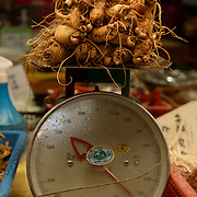 Ginseng is weighed on a scale in Deokpo Market in Busan, South Korea.