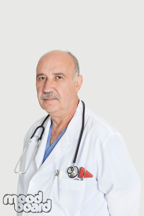 Portrait of serious senior medical practitioner over gray background
