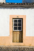 Typical quaint house with old front door in cobbled stone street in Evora, Portugal