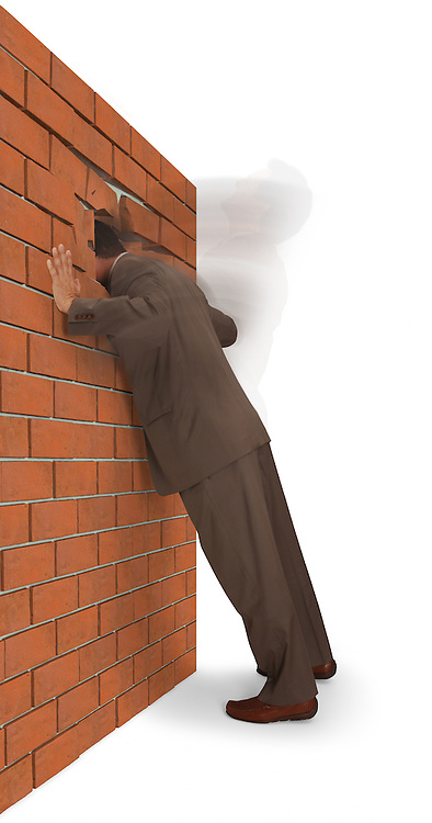 Man slamming his head into a brick wall, isolated on a white background