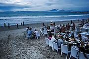 BALI, INDONESIA; APRIL 26, 2015: Tourists have dinner at restaurants along Jimbaran beach on Sunday, April 26, 2015.