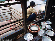 Floating Lives on the Tonle Sap - the lady of the floating house prepares breakfast. This back room is used for cooking, washing dishes, bathing and as a toilet – a problematic combination.