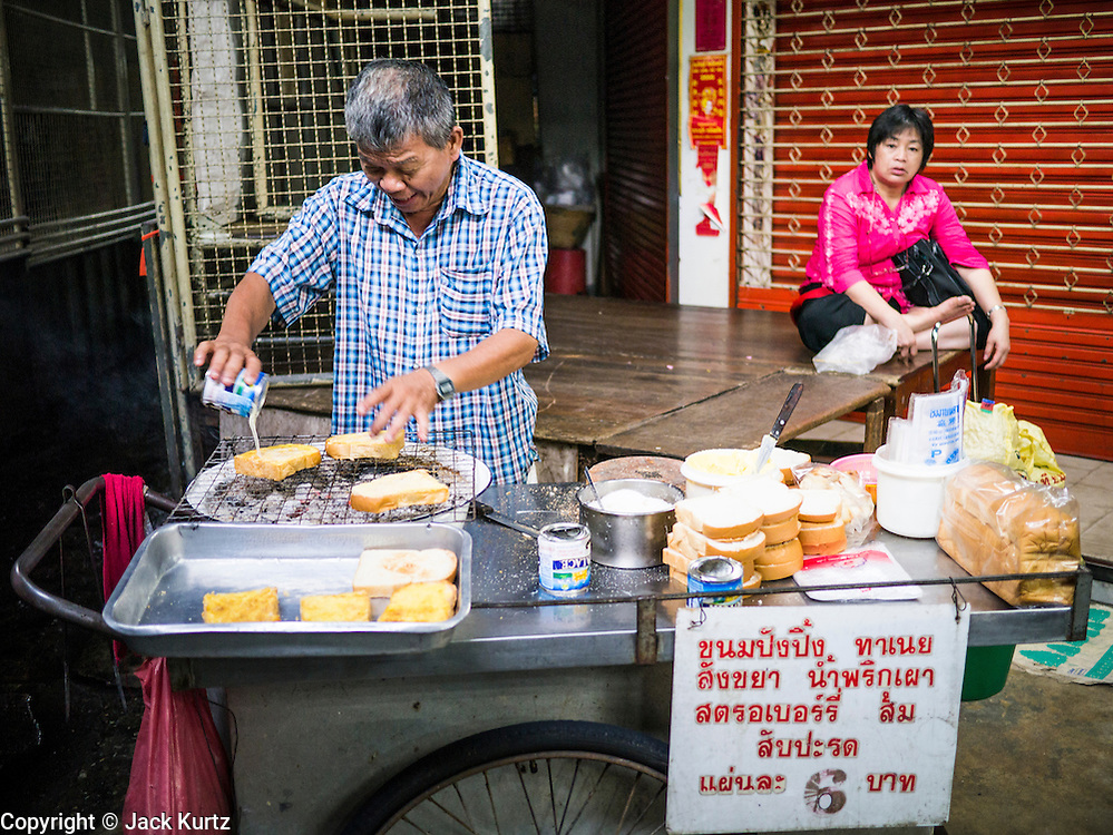 30 MAY 2013 - BANGKOK, THAILAND:   A food vendor makes grilled bread with condensed milk and sugar in Bobae Market in Bangkok. Bobae Market is a 30 year old famous for fashion wholesale and is now very popular with exporters from around the world. Bobae Tower is next to the market and  advertises itself as having 1,300 stalls under one roof and claims to be the largest garment wholesale center in Thailand.   PHOTO BY JACK KURTZ