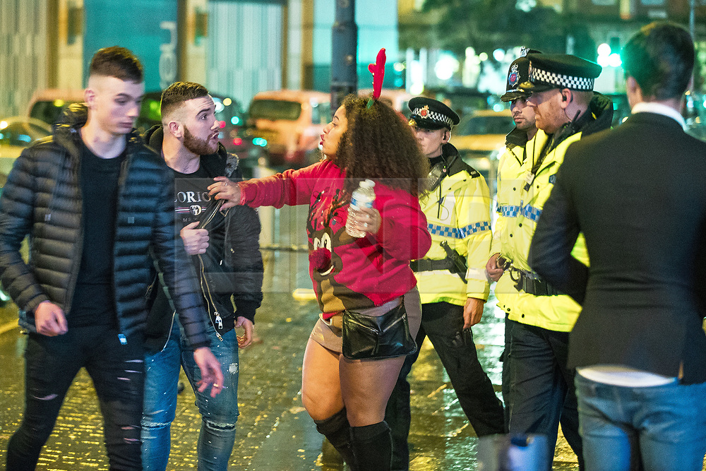 """© Licensed to London News Pictures . 23/12/2017. Manchester, UK. A woman wearing festive red reindeer antlers attempts to encourage a man to leave the area outside the Printworks after police intervene to break up a fight . Revellers out in Manchester City Centre overnight during """" Mad Friday """" , named for being one of the busiest nights of the year for the emergency services in the UK . Photo credit: Joel Goodman/LNP"""