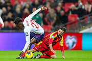 England forward Tammy Abraham brought down by Montenegro midfielder Deni Hočk during the UEFA European 2020 Qualifier match between England and Montenegro at Wembley Stadium, London, England on 14 November 2019.