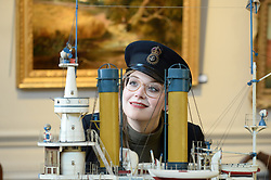 Bonham's worker Jaine Heggie dons a captains cap in preparation for the nautical collection auction at Bonham's in Edinburgh on November 15th pictured inspecting a mid 20th century model of Russian battleship 'Admiral Oushavov' which is up for sale.<br /> <br /> &copy; Dave Johnston/ EEm