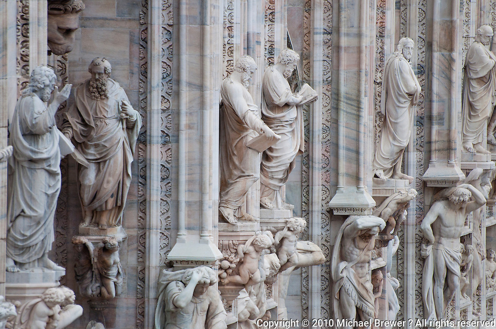 Milan, Italy, Duomo Cathedral. Stone Statuary on the front exterior of the building - figures of learned men on pedestals with partly clothed figures supporting them.