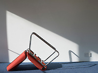 Upturned office chair casting shadow on wall