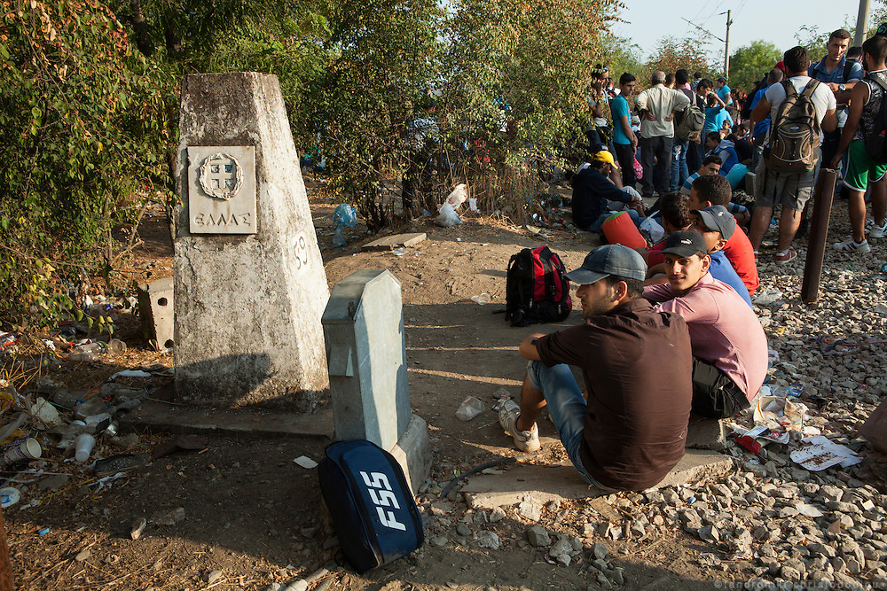 Refugees waiting by the cone that marks the Greek border, for their turn to cross. Busses come regularly to pick them up after they cross. <br /> Refugees arrive at Eidomeni border by bus and some times on foot. There they can cross to the republic of Macedonia on foot.