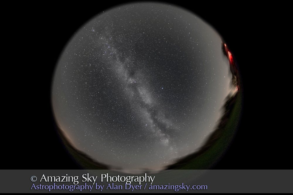 An image of the entire sky and summer Milky Way, from home in southern Alberta, from my backyard, on September 12, 2015. The night was clear but not that transparent, as some humidity and haze added more than usual horizon glows reflecting yellow light pollution. But there was no aurora, in a week filled with auroras every night. The prominent red nebula overhead is the North America Nebula in Cygnus. South is at bottom, west to the right. <br /> <br /> This is a stack of 5 exposures, each 6 minutes at f/4 with the Sigma 8mm fish-eye lens and filter-modified Canon 5D MkII at ISO 1600, all tracked on the iOptron Sky-Tracker. The exposures are average-stacked in a Mean stack mode combination to smooth noise, and yielding the blurred foreground, which comes from all 5 exposures. This version of the image has been processed to make the view better resemble what you see with the unaided eye, in a largely monochrome and softer view than the colourful and high-contrast views commonly presented in astrophotos. Even at that there is more fine structure present in the Milky Way than the unaided eye usually sees, though binoculars beging to reveal that smaller detail. I have left some colours in some stars and in the foreground of landscape scenes.