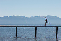 Man running along pier with mountains behind side view