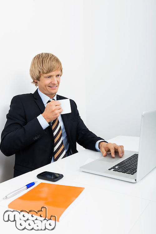 Confident businessman having coffee white using laptop in office