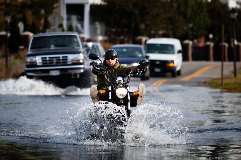 Motorists drive through a flooded section of Llewelyn Avenue near the Lafayette River in Norfolk, Va., on Monday, Oct. 26, 2015. So-called nuisance flooding can get into backyards and happens every high tide in the neighborhood known as Colonial Place. (Photo by Will Parson/Chesapeake Bay Program)