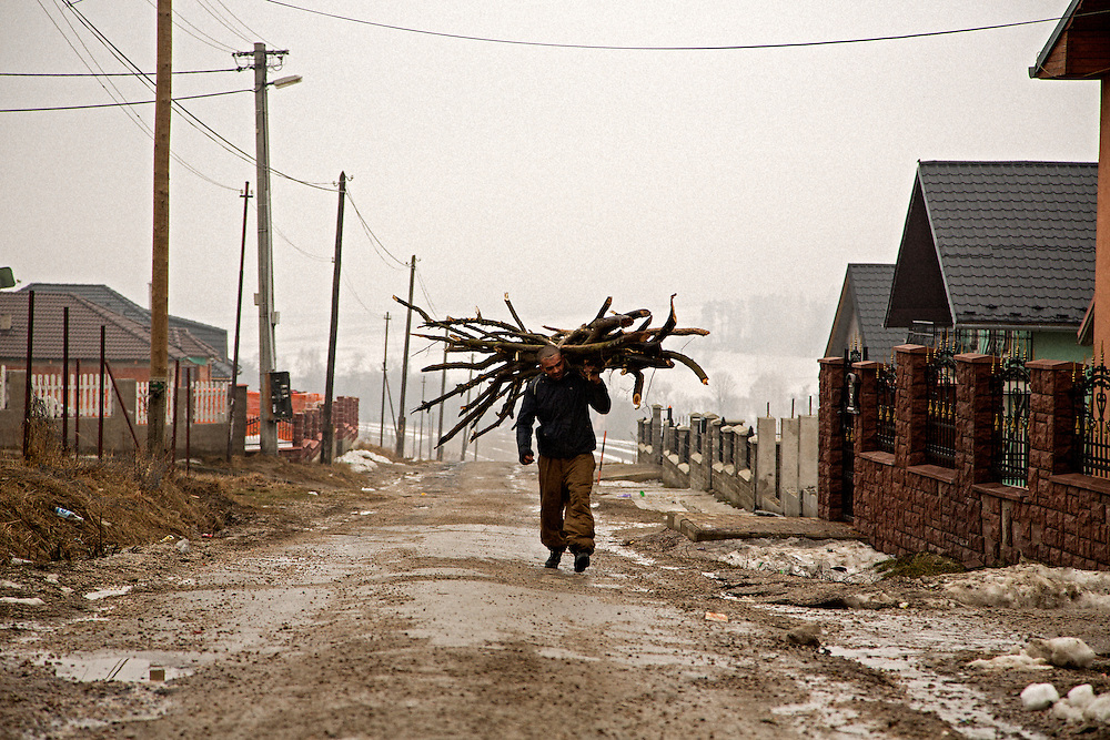 A man carries wood in to the large Roma settlement in the northern Slovakian town of Stráne pod Tatrami which sits at the base of the Tatra Mountains.